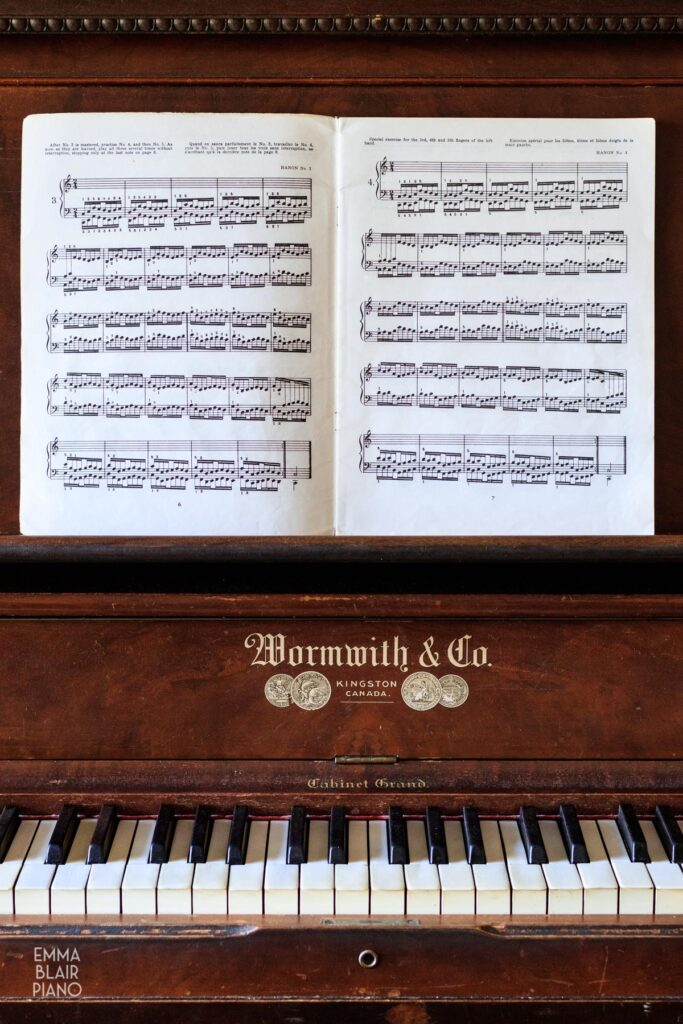 book of Hanon exercises open on a piano music stand