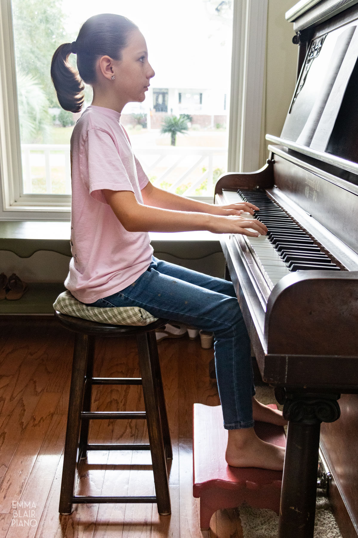 girl sitting at the piano with a footstool