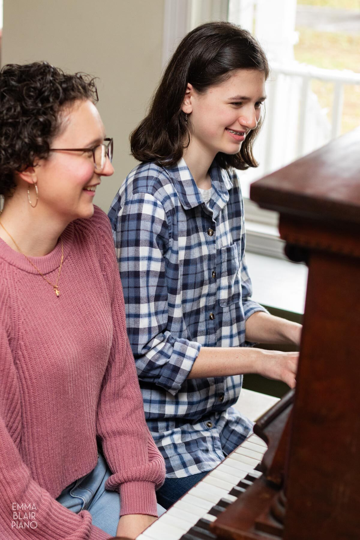 teenage girl playing the piano and smiling beside her piano teacher