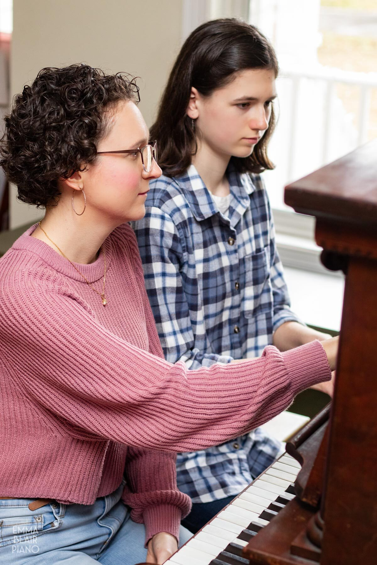 piano teacher pointing out something to her student