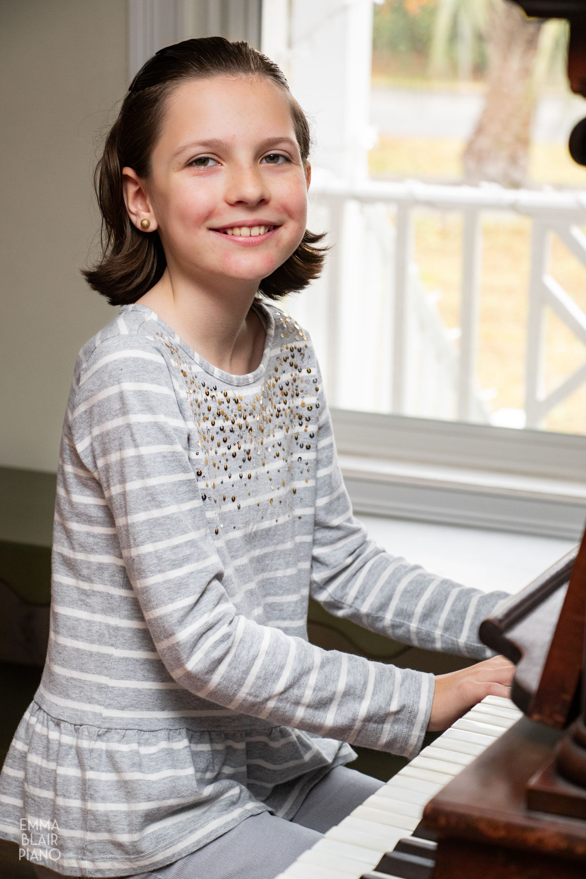 young girl smiling at the piano