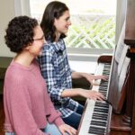 piano teacher sitting beside her student at the piano