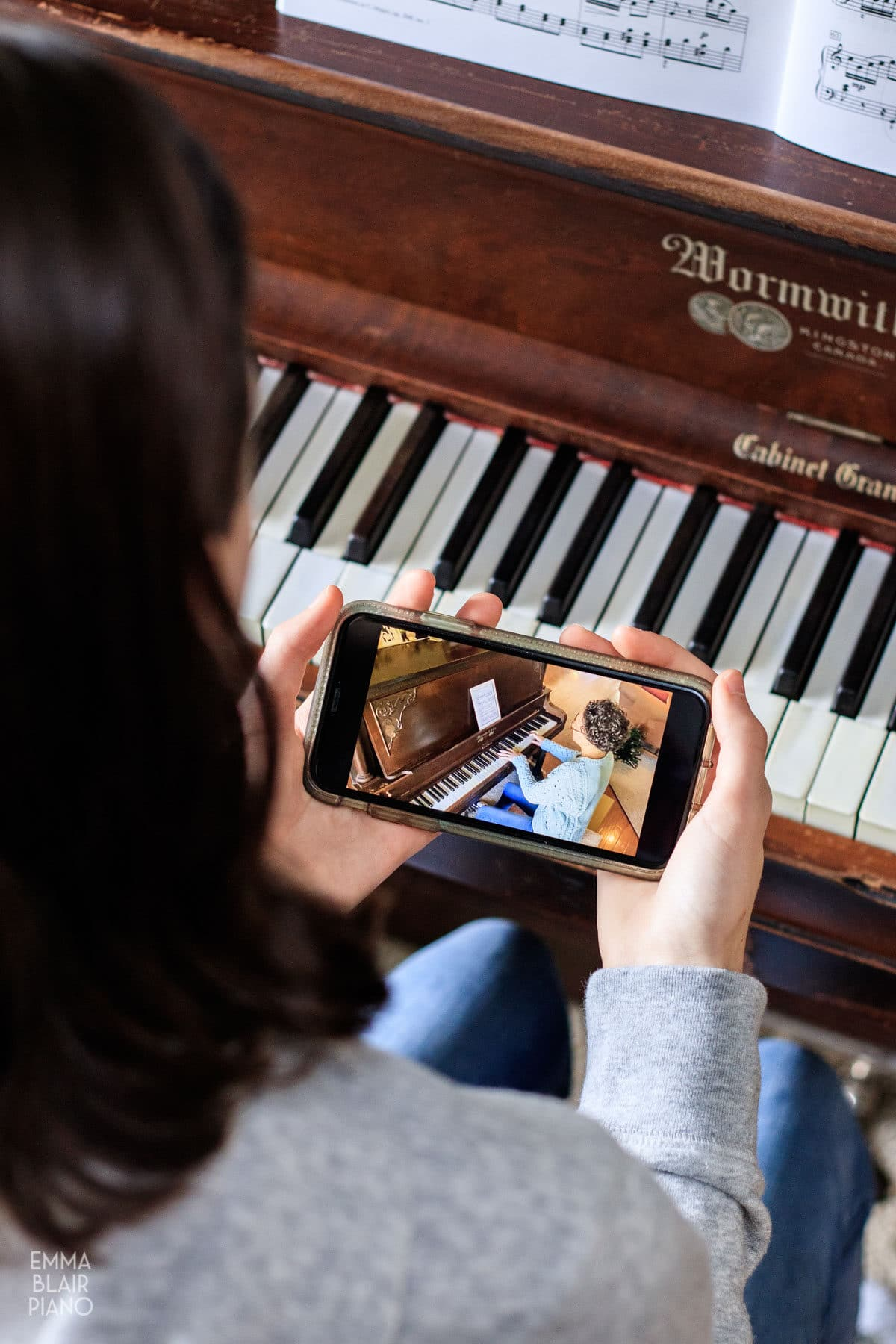 teenage girl watching a piano video on a cell phone