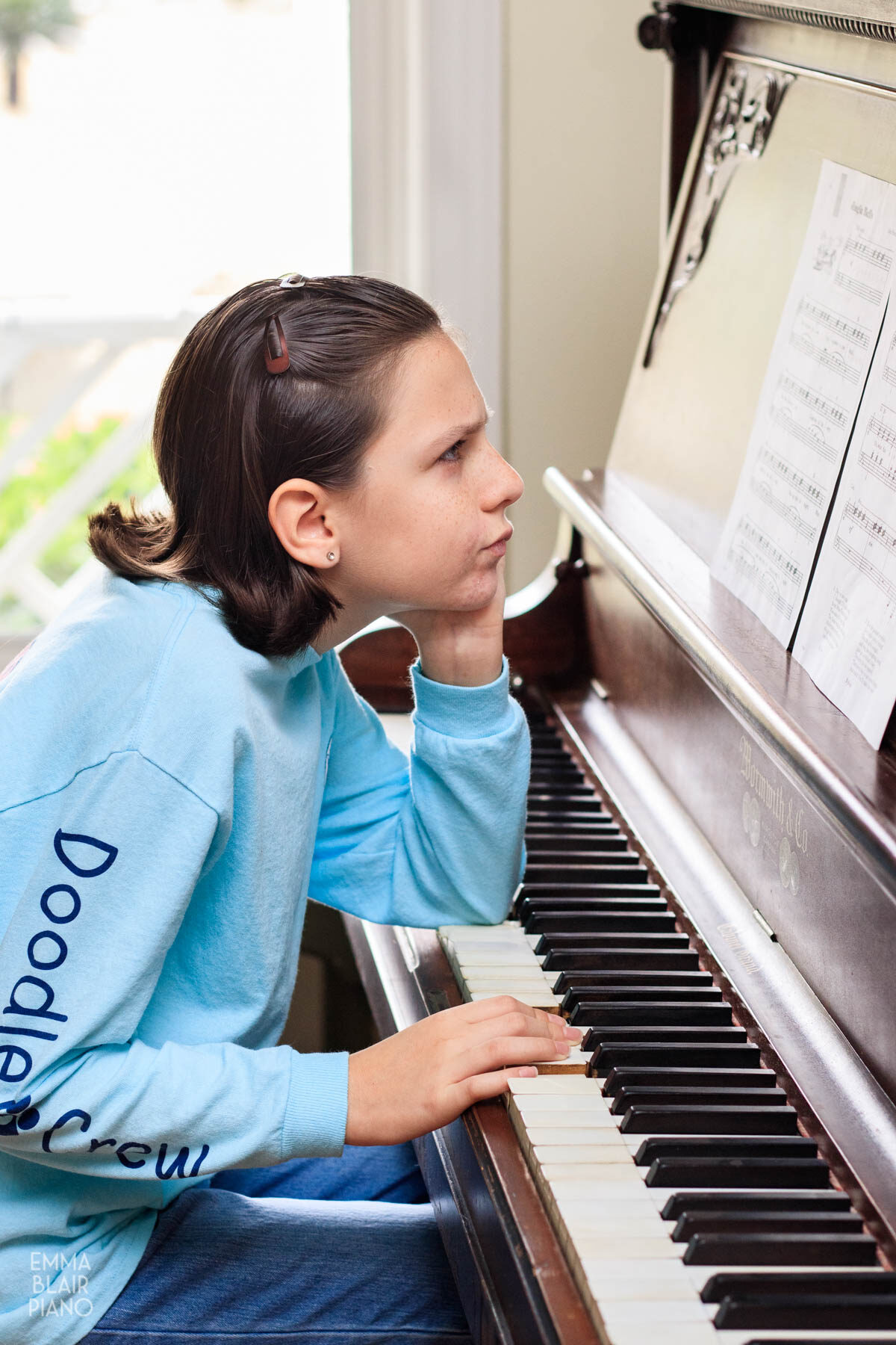 girl frowning at sheet music while playing the piano