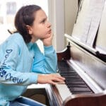 girl frowing while trying to play the piano