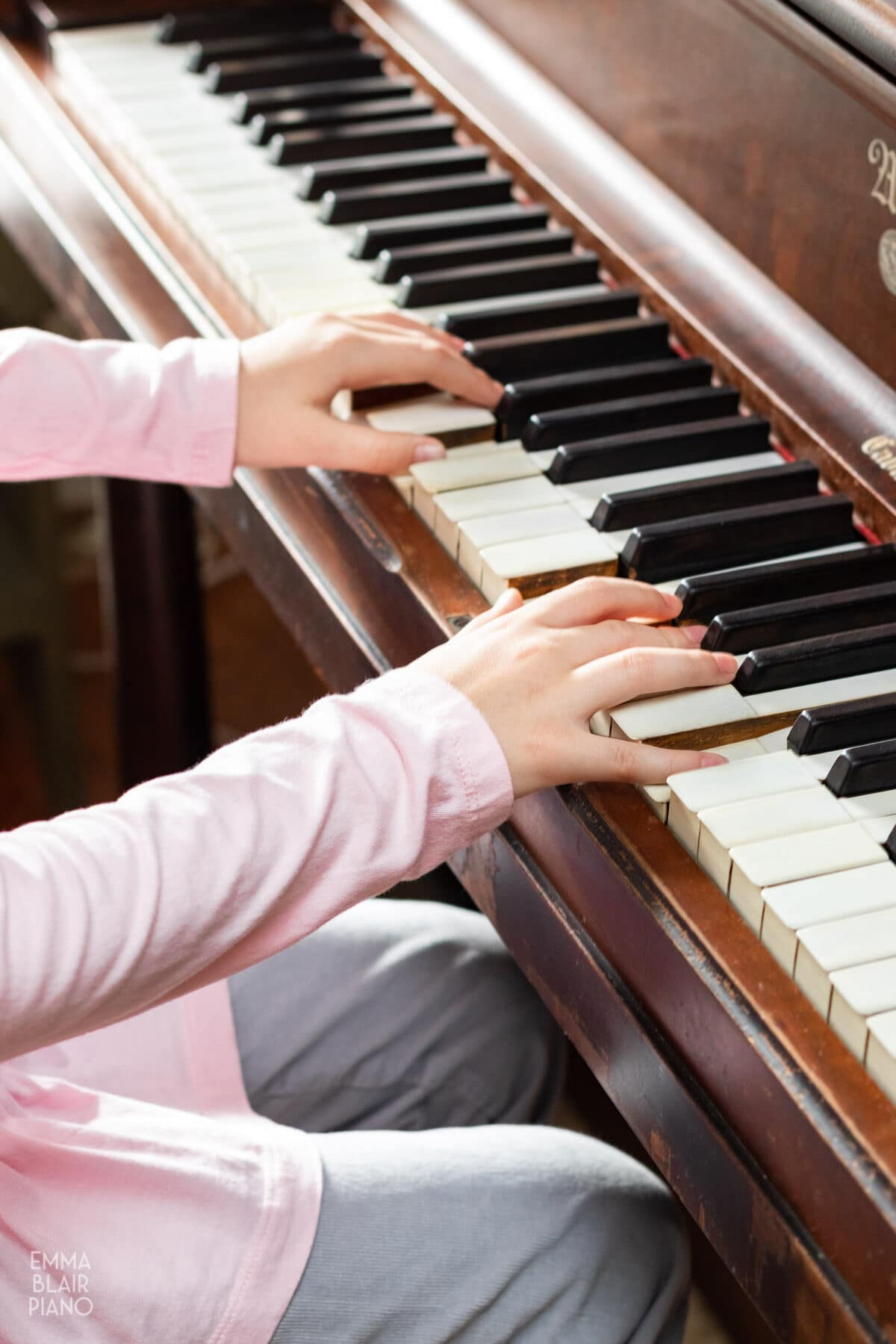 young girl's hands playing an upright piano