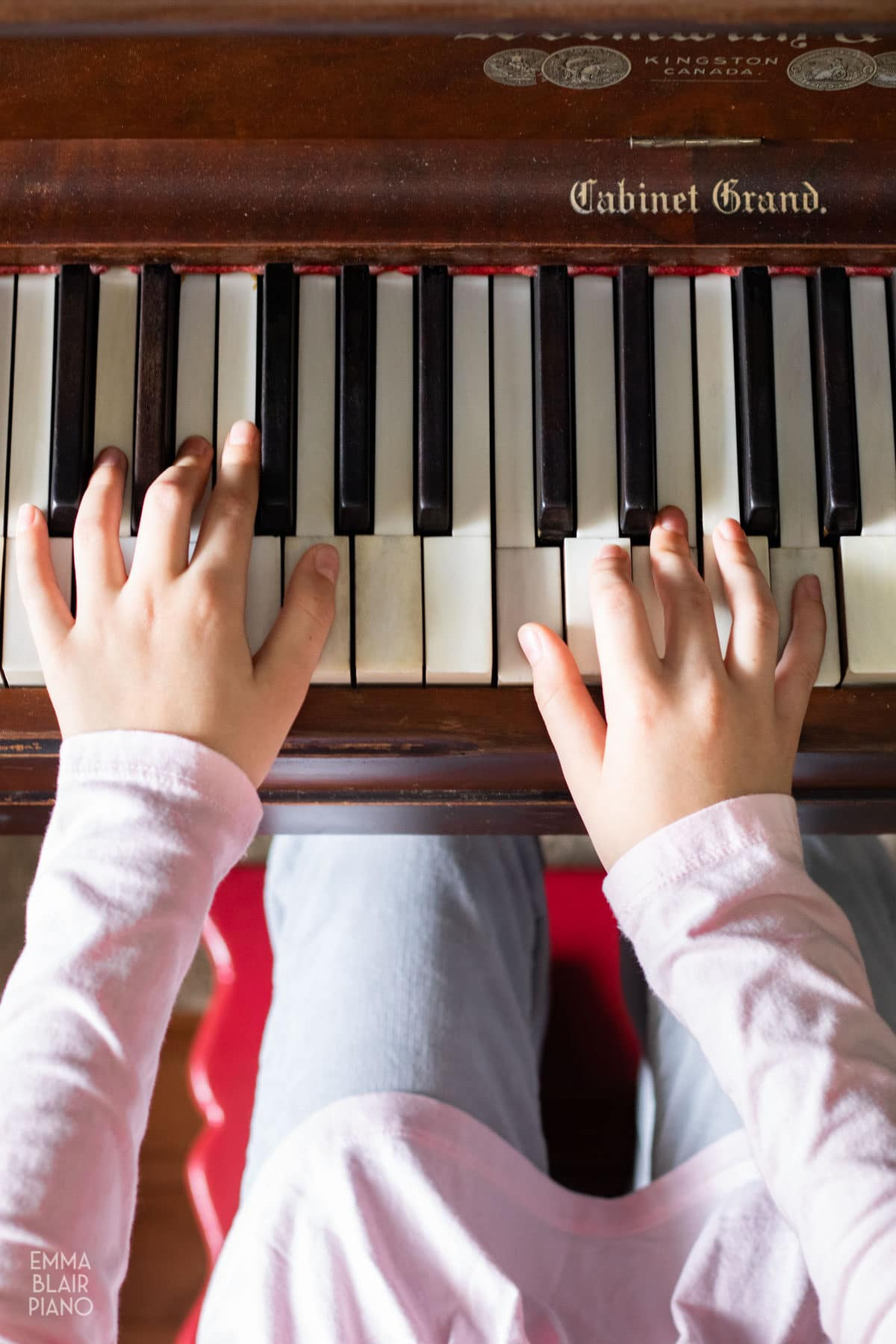 top view of a young girl's hands playing the piano
