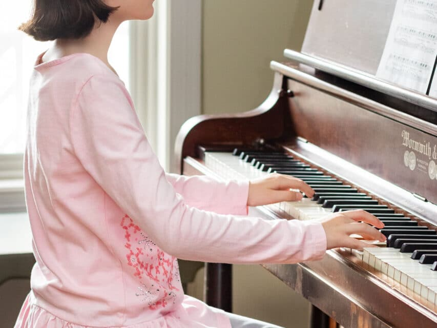 young girl playing an upright piano