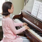 young girl performing a piece on an upright piano