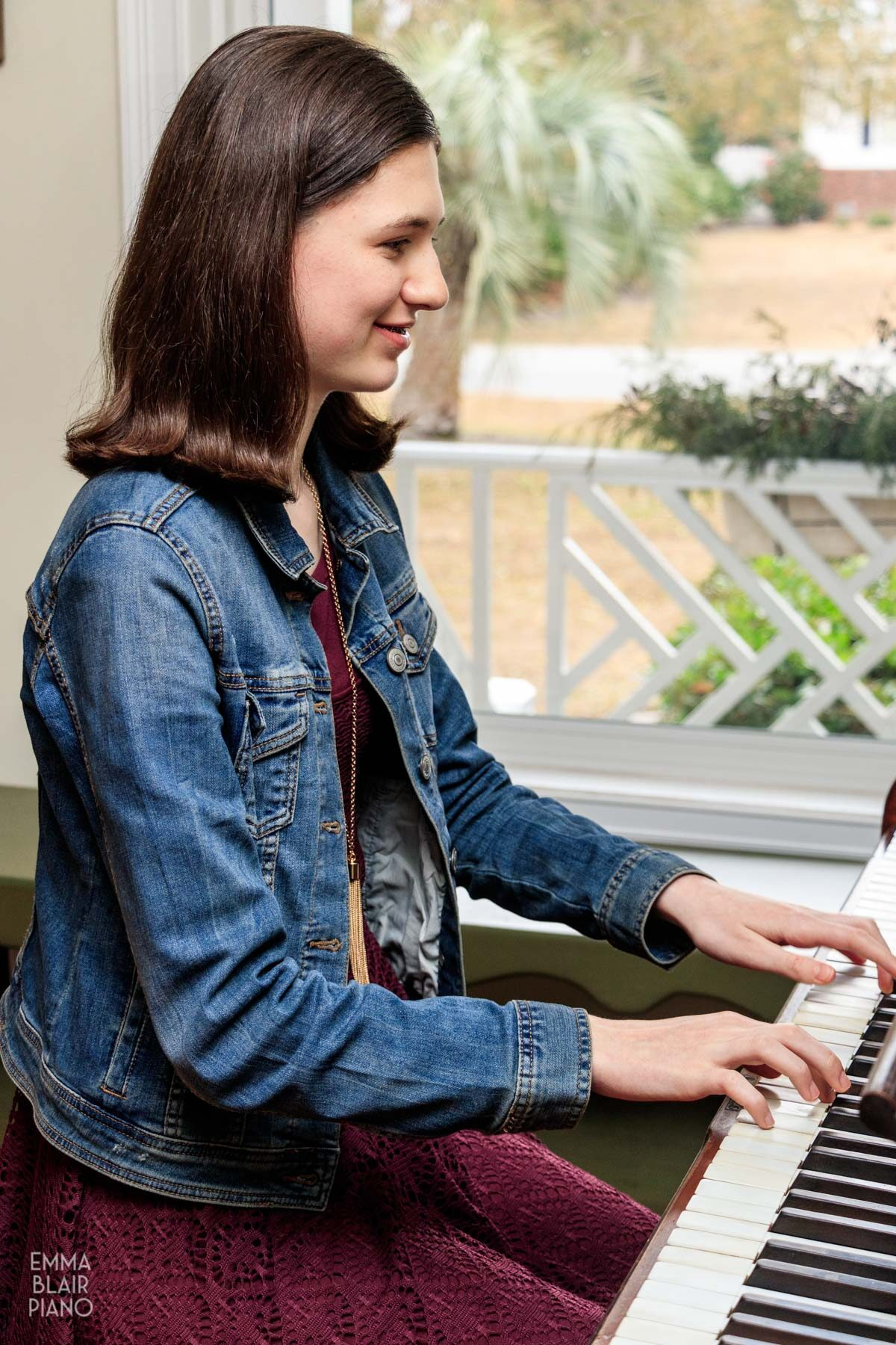 teenage girl playing the piano and smiling