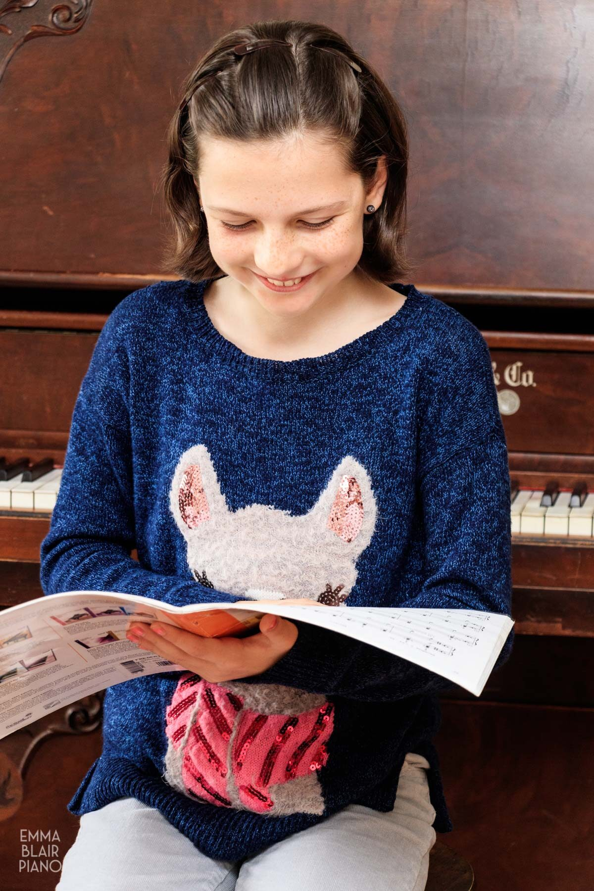 young girl smiling while holding a book of piano music