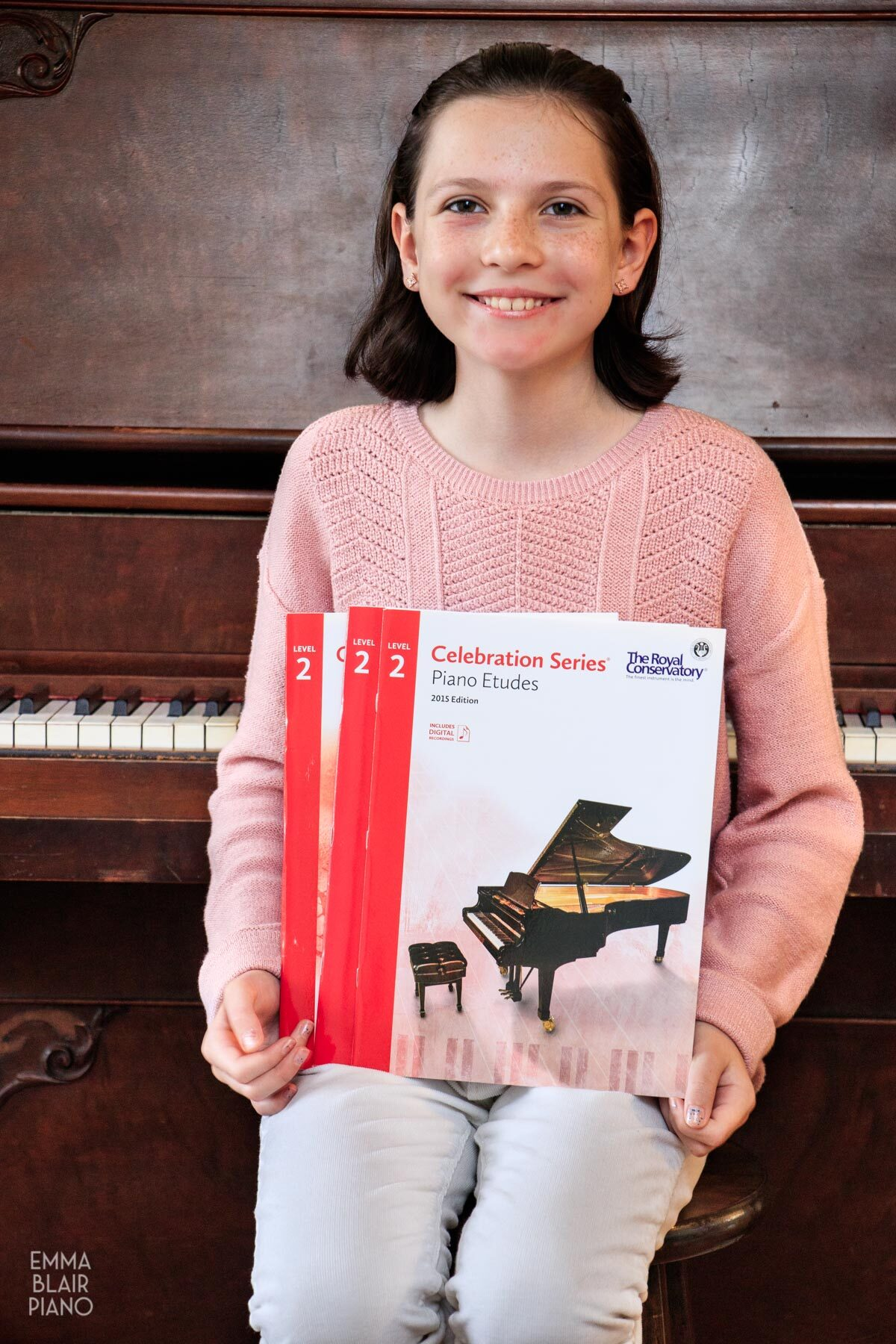 smiling girl holding music books in front of the piano