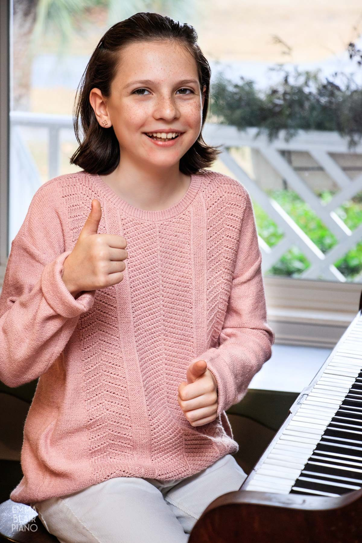 young girl smiling, sitting at the piano, and doing thumbs up