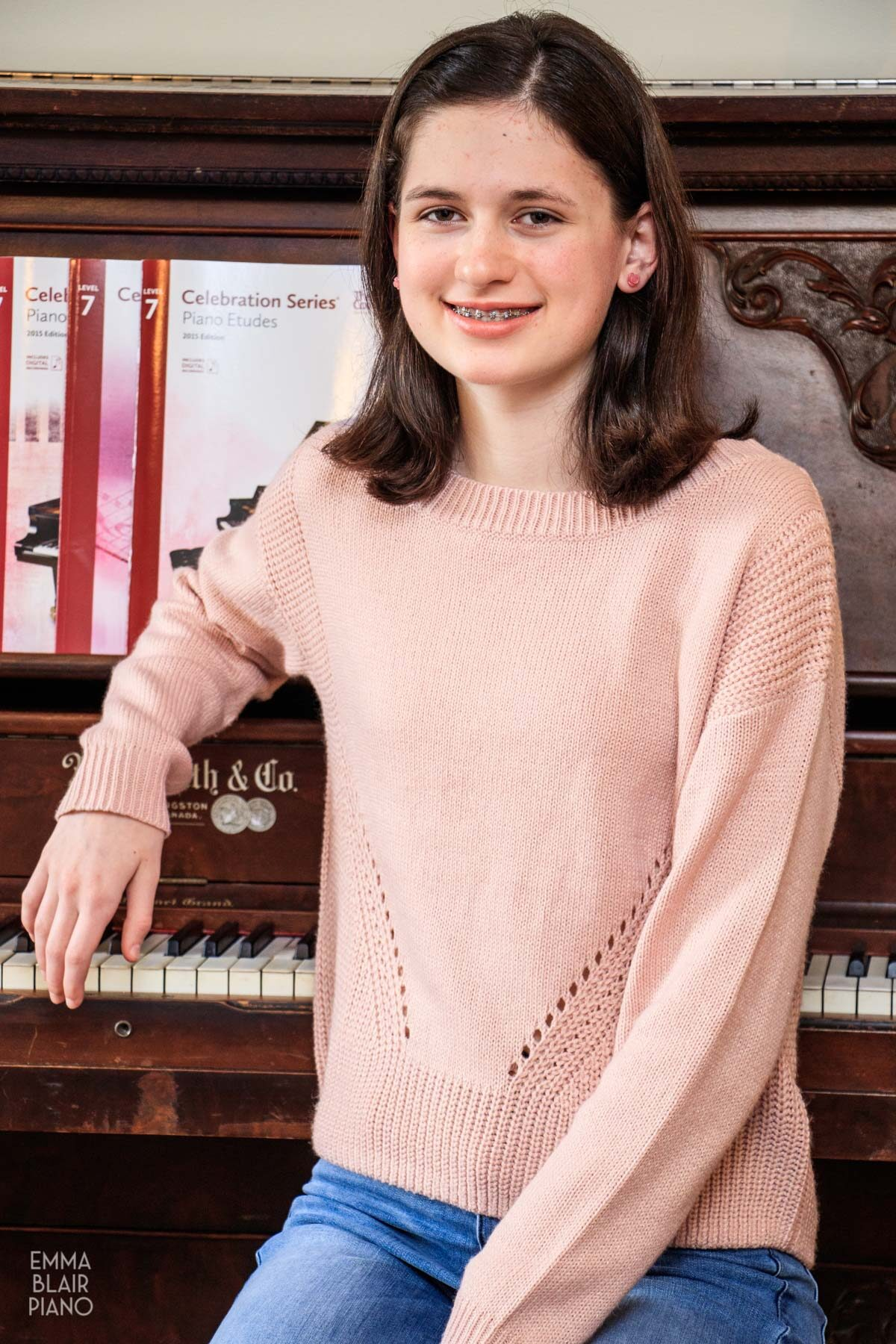teenage girl leaning on the piano and smiling