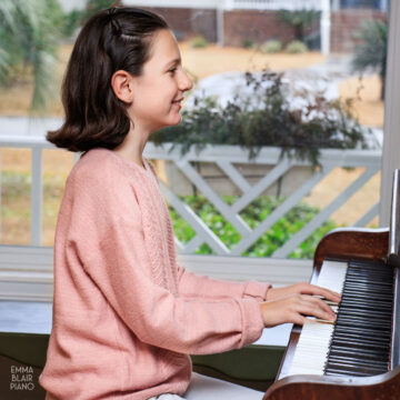 young girl playing the piano and smiling