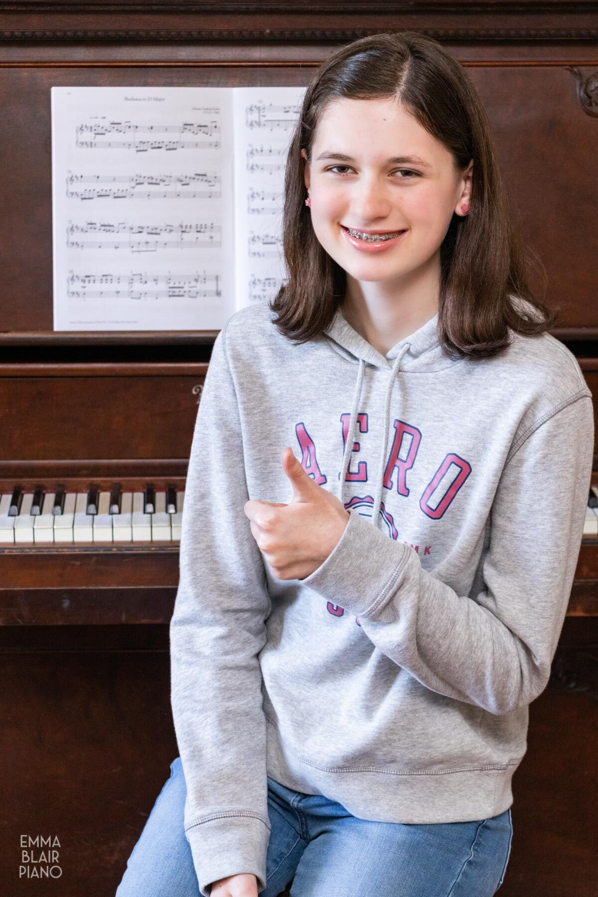 teenage girl smiling and sitting at the piano doing a thumbs up