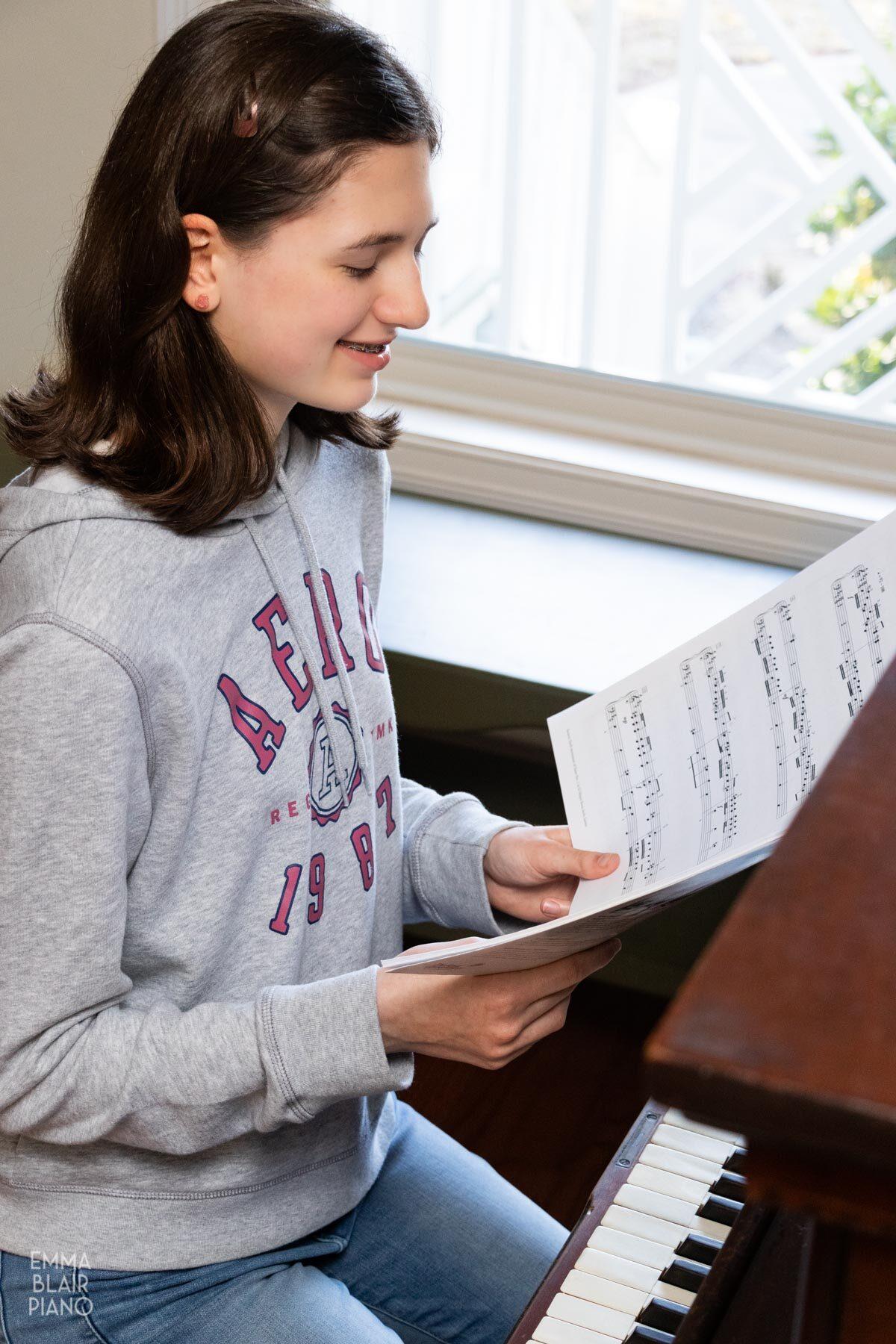 teenage girl looking at a music book at the piano