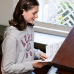 teenage girl smiling as she looks at a book of piano music