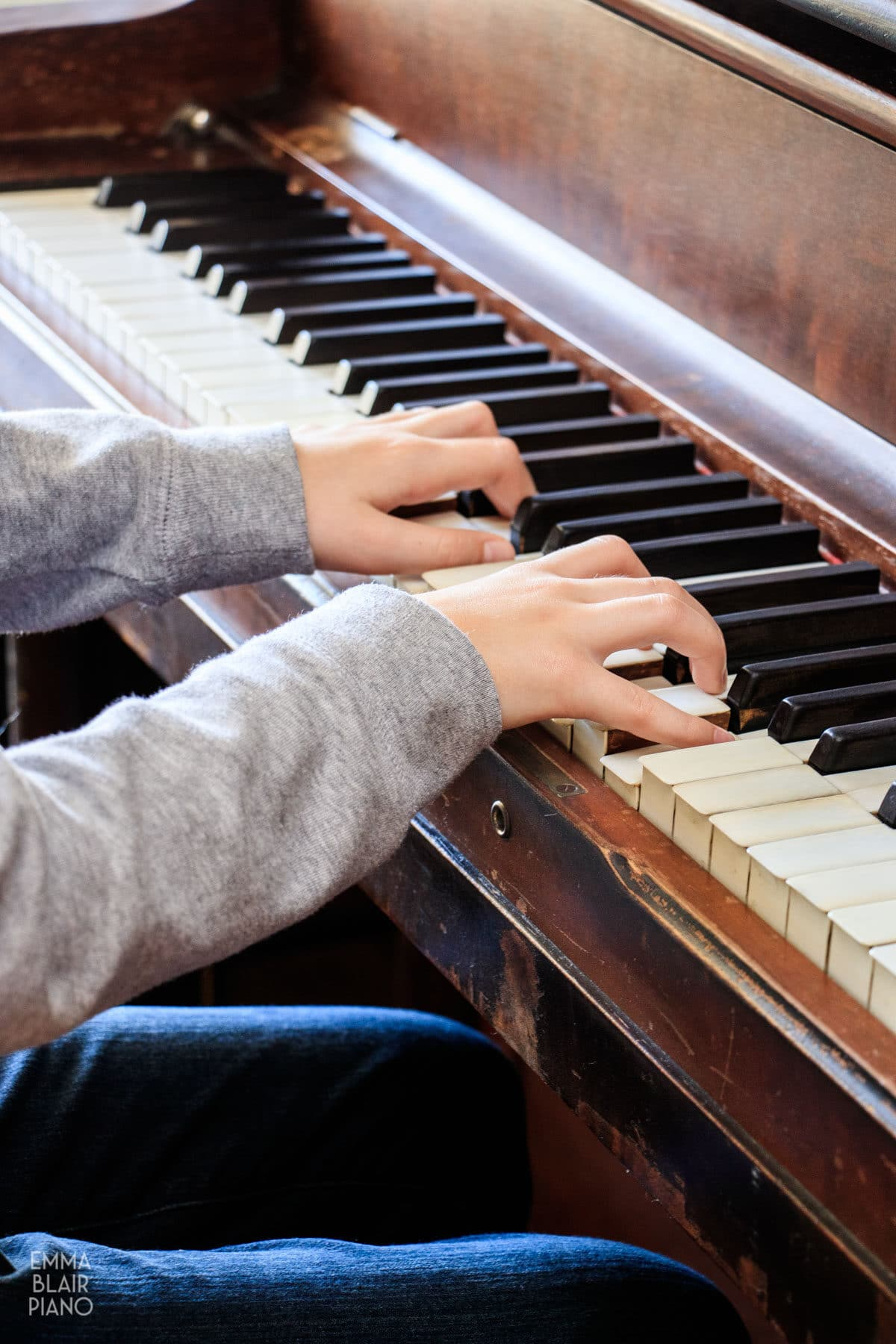 side view of a girl playing C major chords at a piano