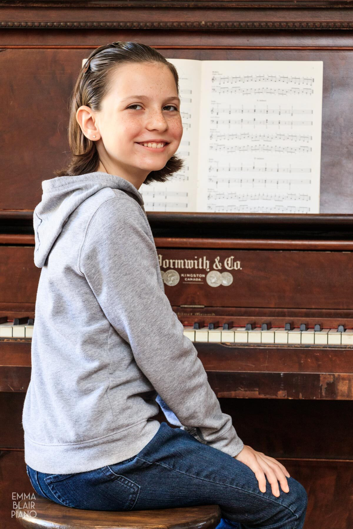 girl sitting at the piano with a book of triads on the music stand