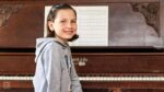 young girl sitting at the piano with music on the stand