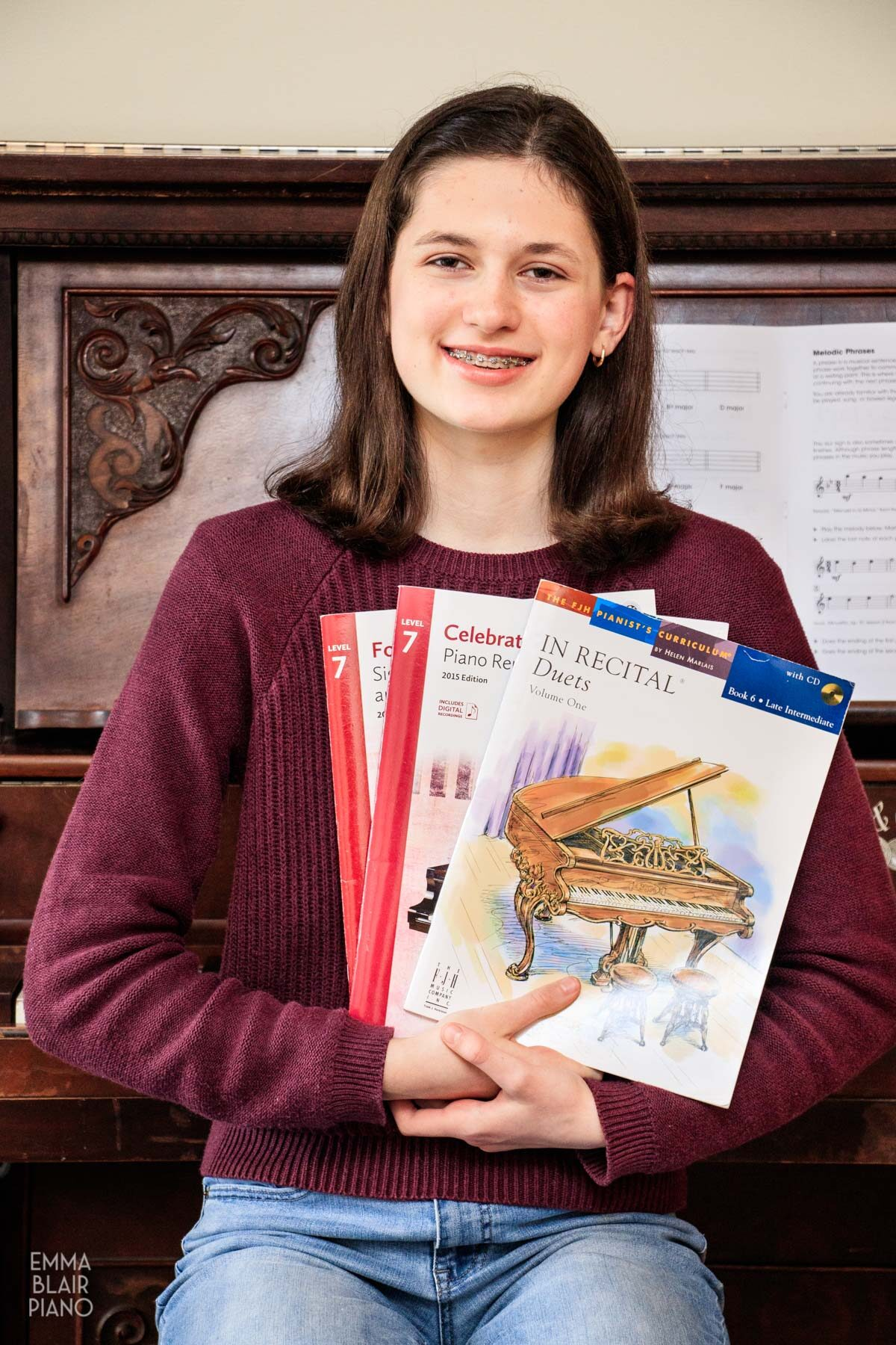 teenage girl holding piano music books and smiling