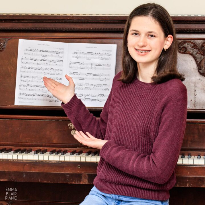 teenage girl pointing to piano music and smiling