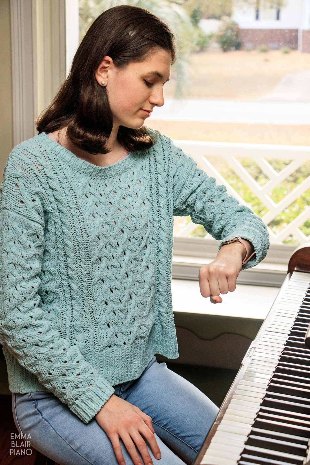 teenage girl checking her watch as she sits at the piano
