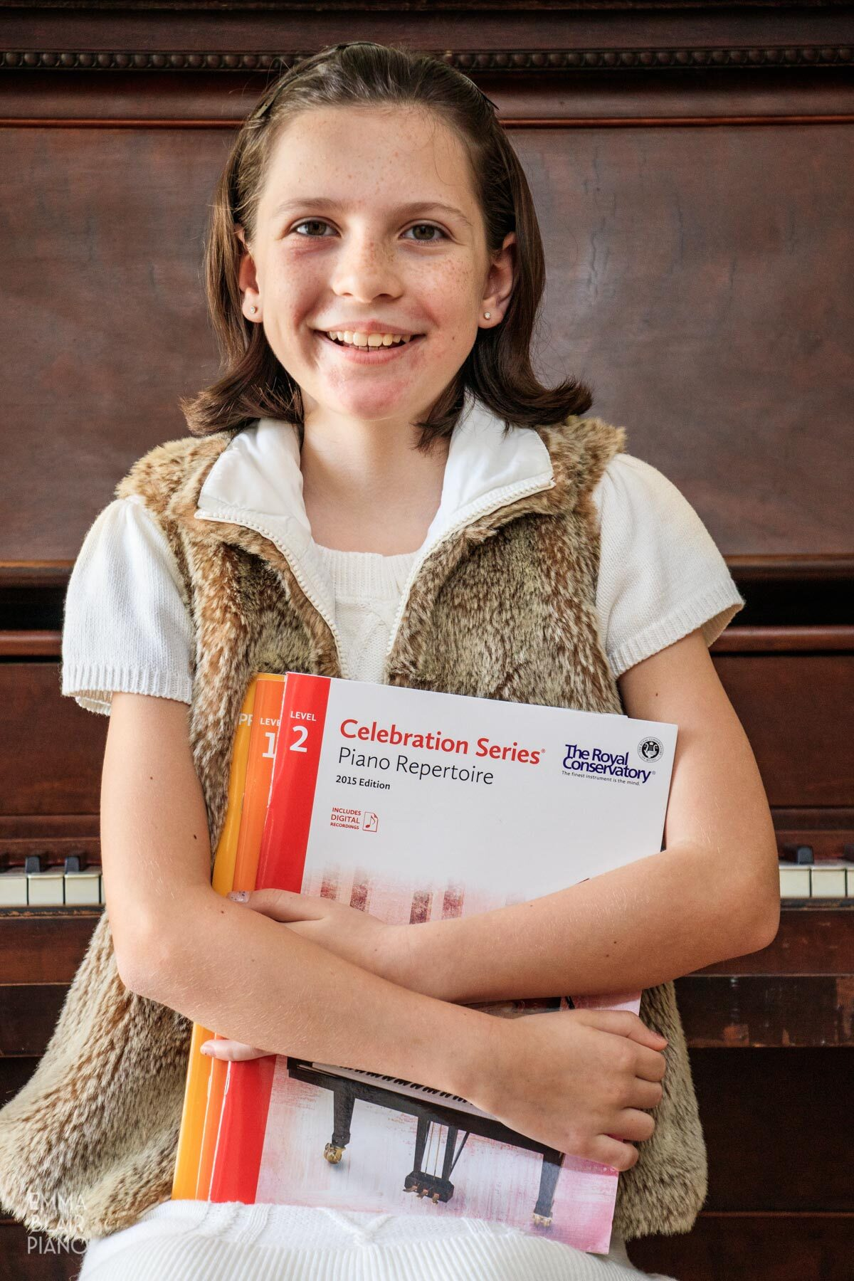 smiling girl holding a stack of piano books
