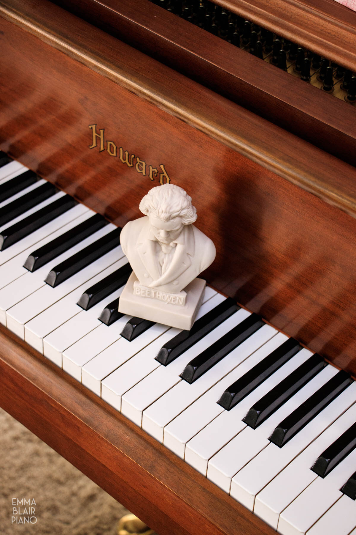 small bust of Beethoven sitting on a piano keyboard