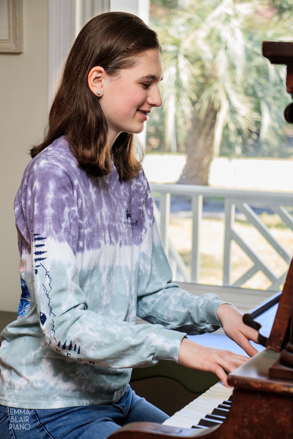 teenage girl playing the piano