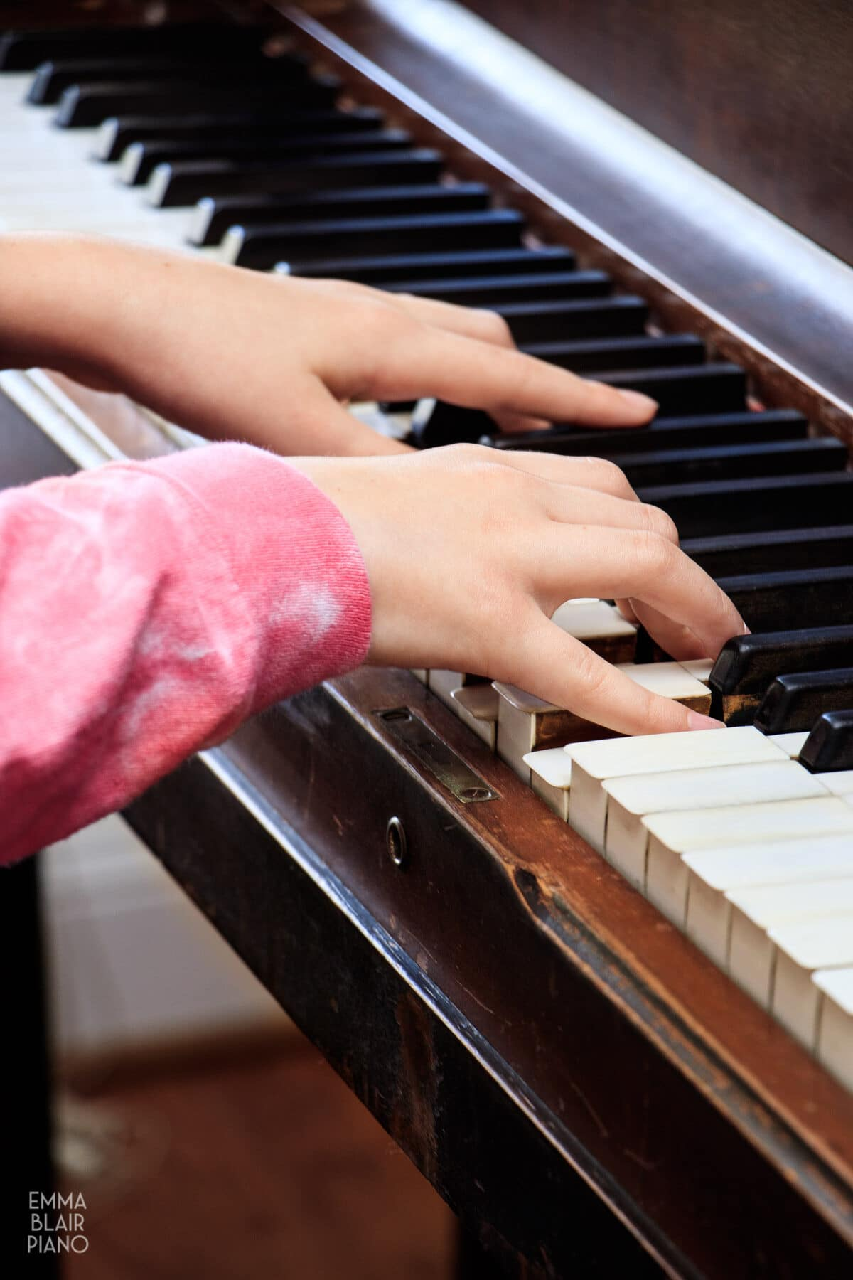 closeup of a young girl's hands playing the piano