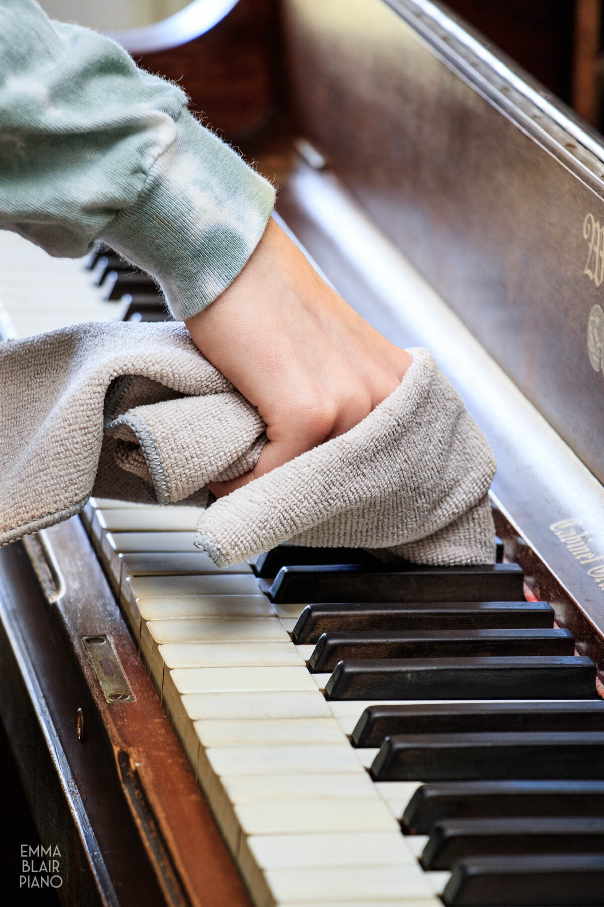 teenage girl cleaning the piano keys with a microfiber cloth