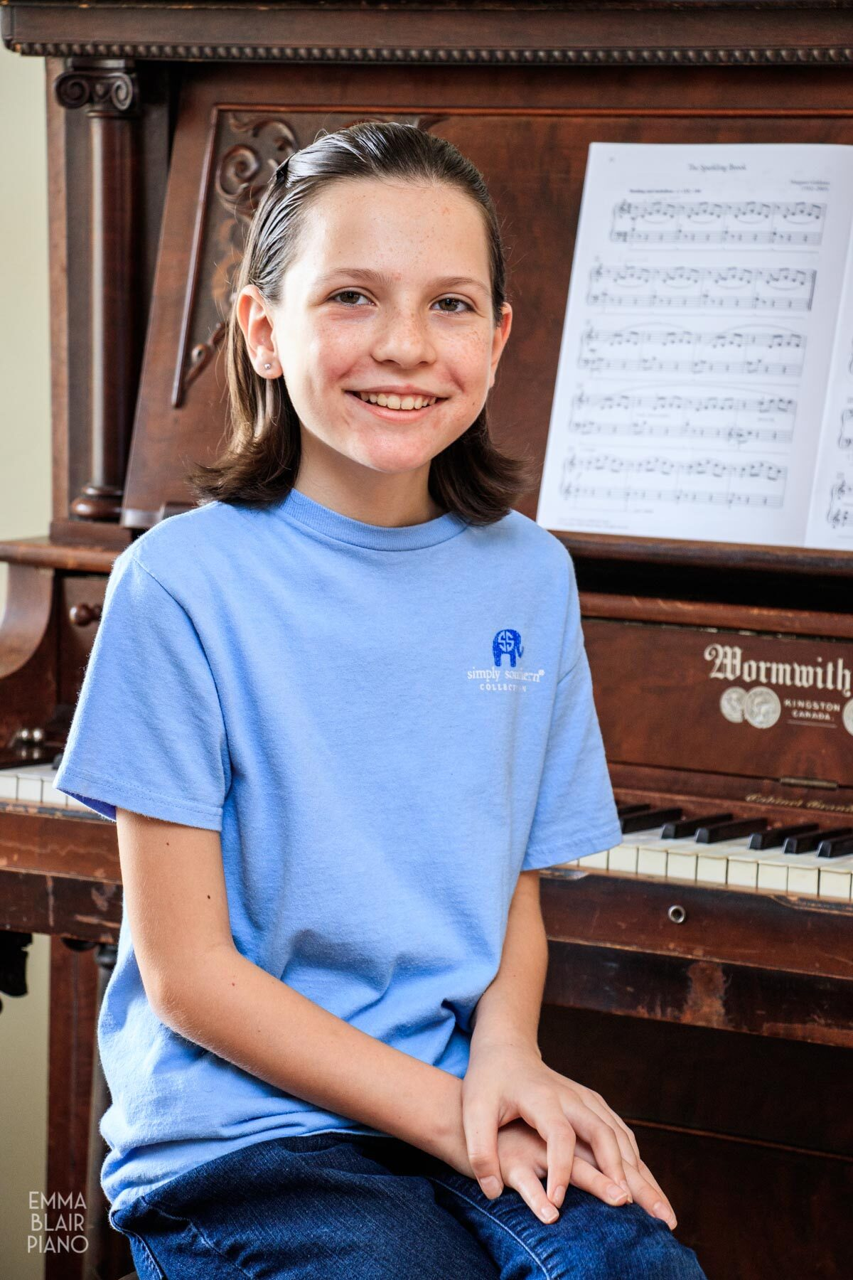 young girl sitting at the piano and smiling