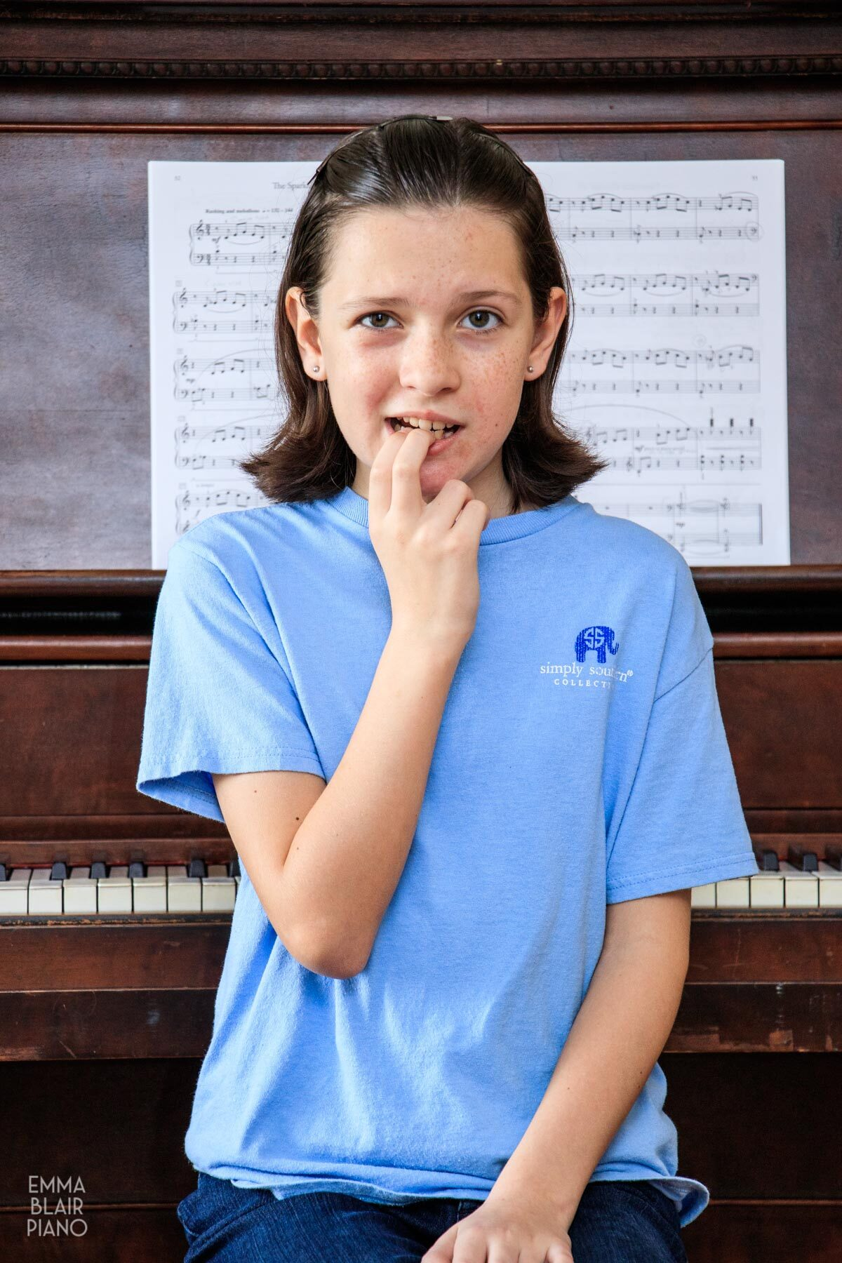 young girl sitting at the piano looking nervous