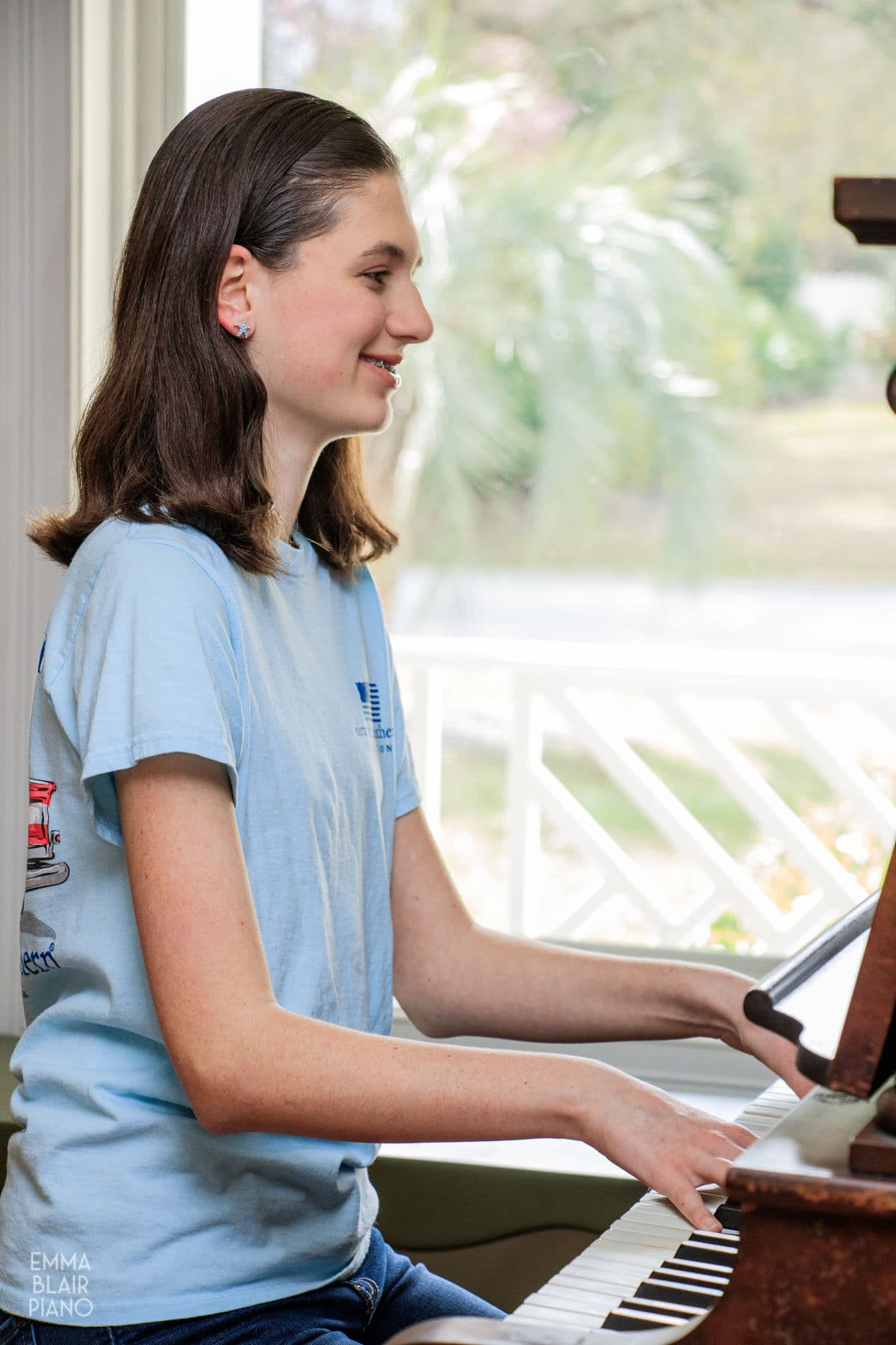 teenage girl playing the piano with a smile and confidence