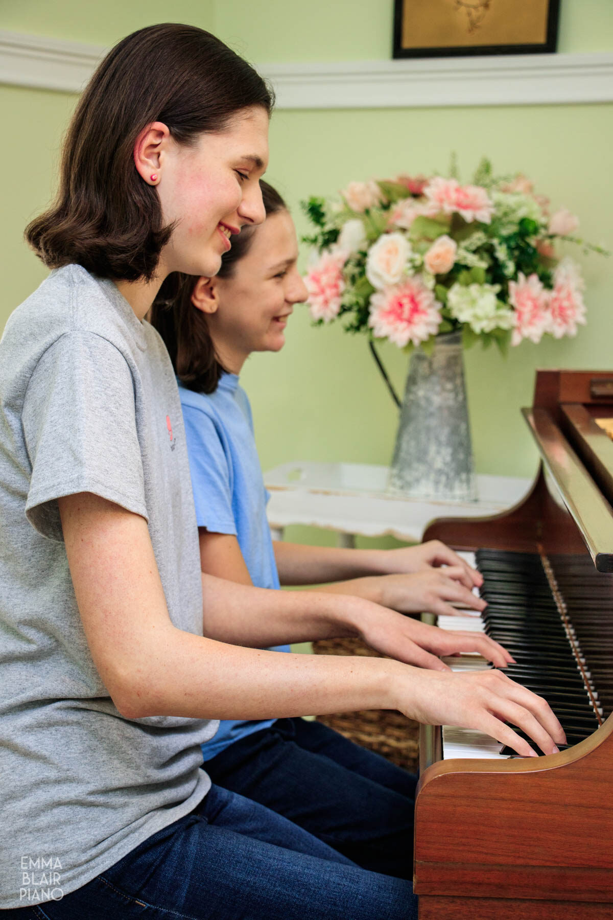 two girls playing a piano duet and smiling