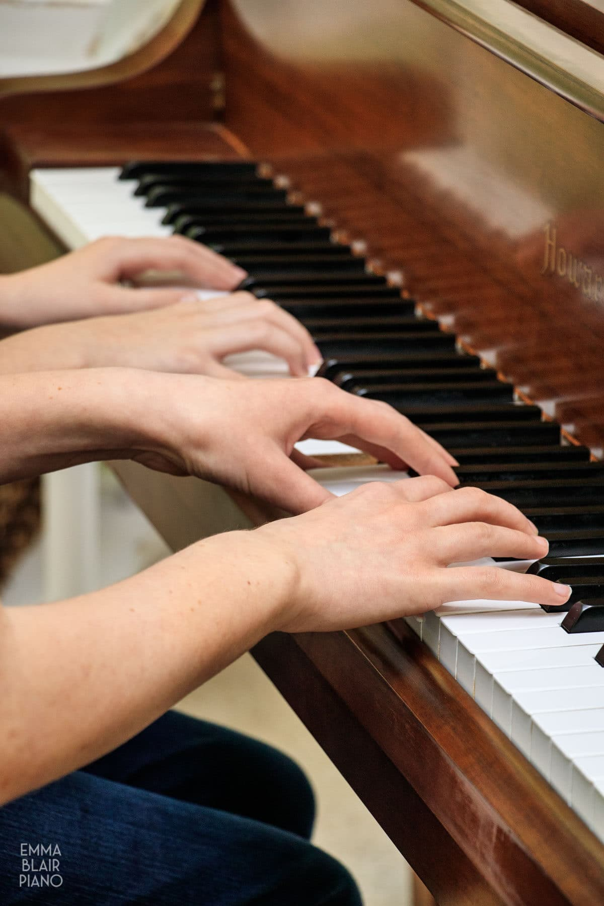 closeup of four hands playing a piano duet