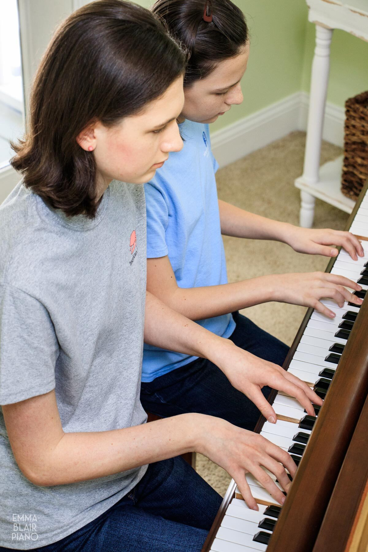 two girls playing a piano duet at a grand piano
