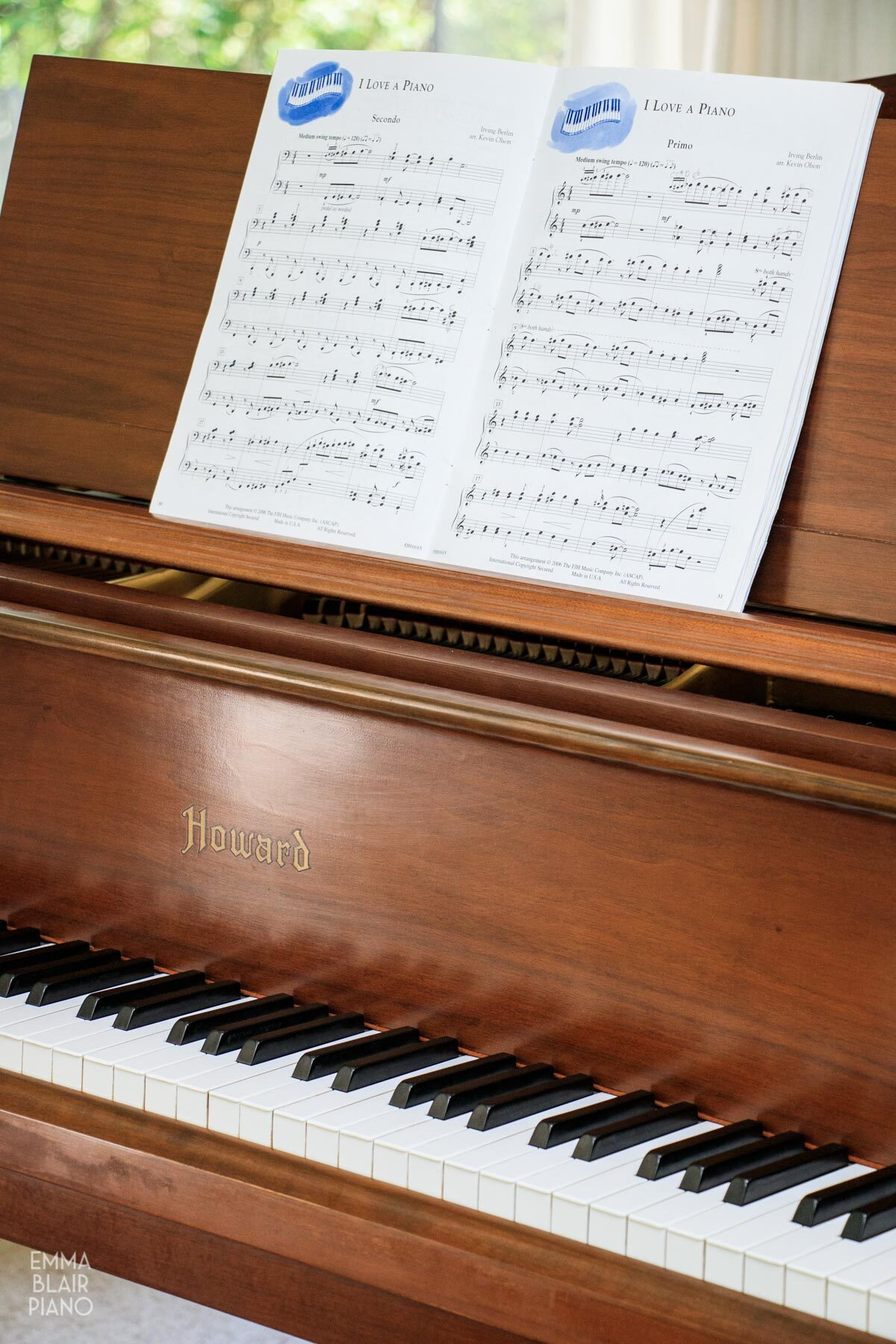 a book of duet piano music on the piano's music stand