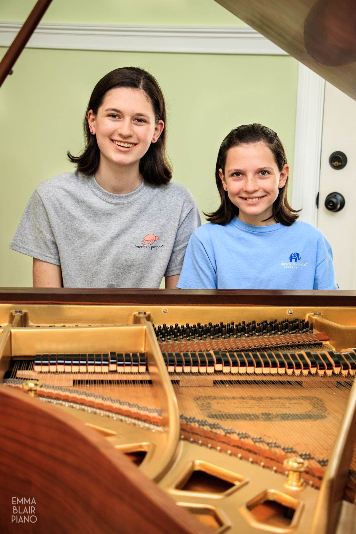two girls sitting at a grand piano and smiling