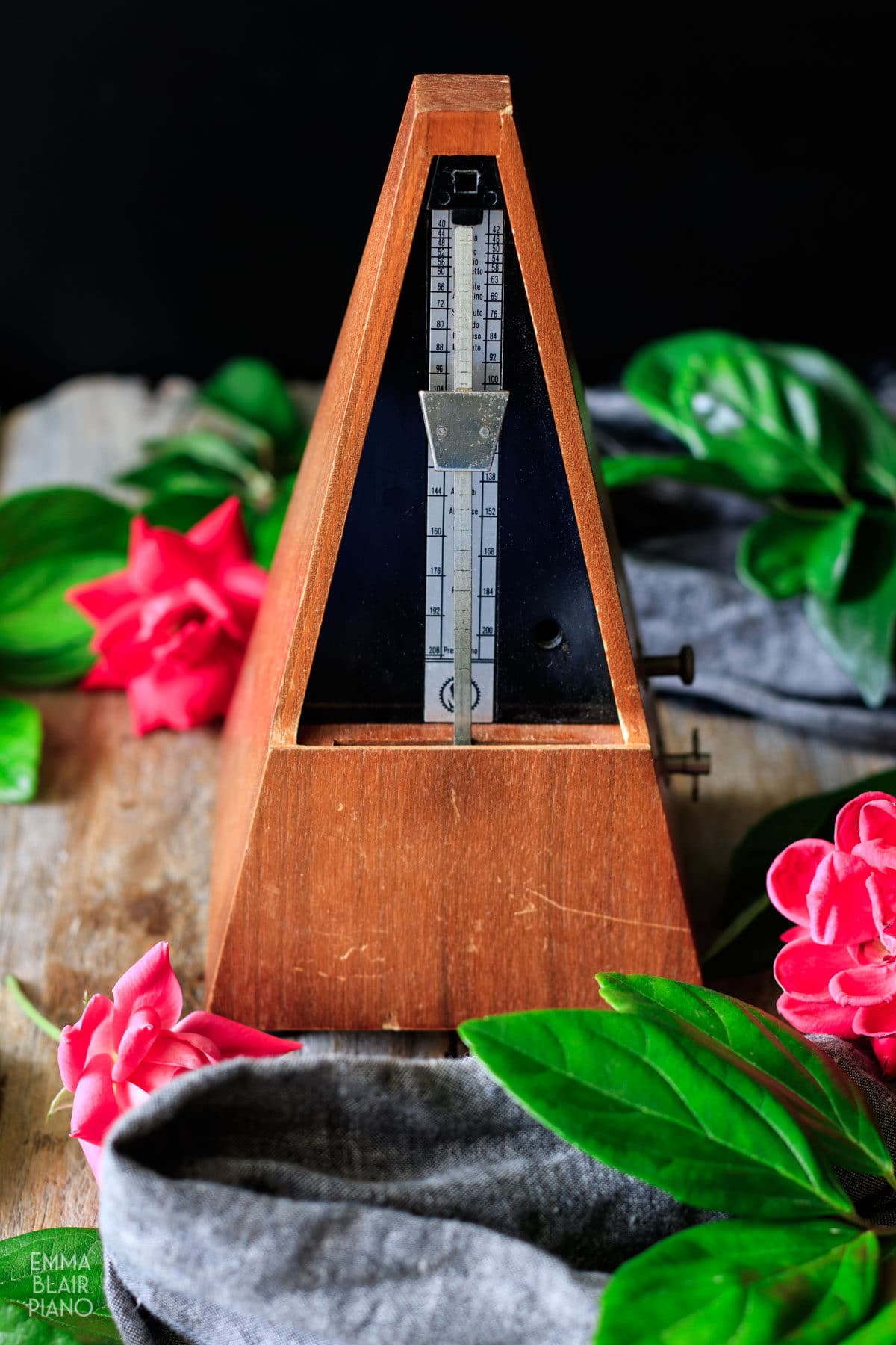 wooden metronome with pink roses and gray linen