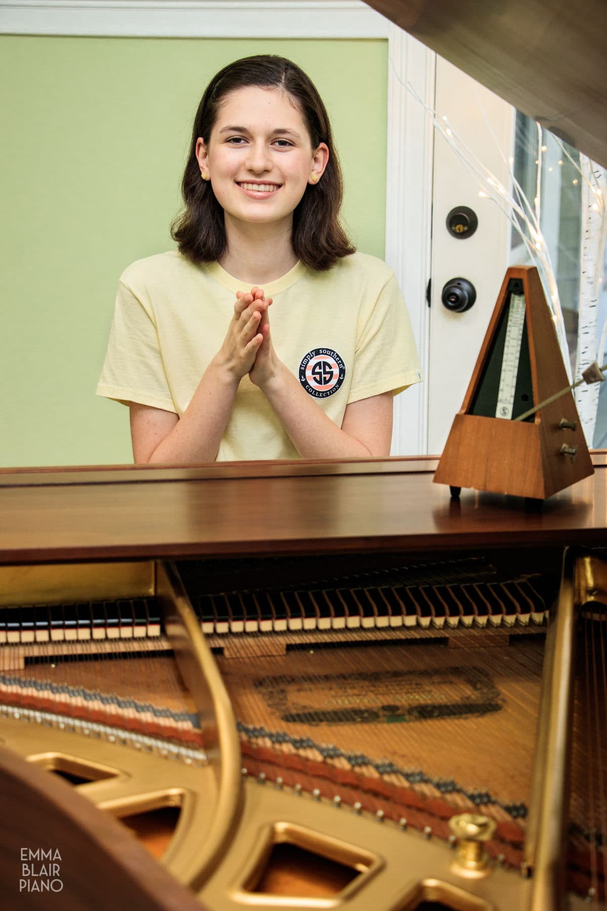 teenage girl clapping a rhythm with a metronome at the piano