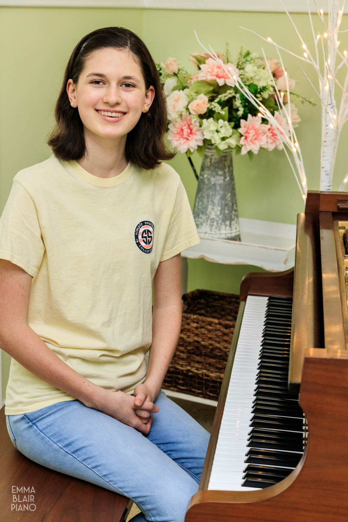 teenage girl sitting at a grand piano and smiling