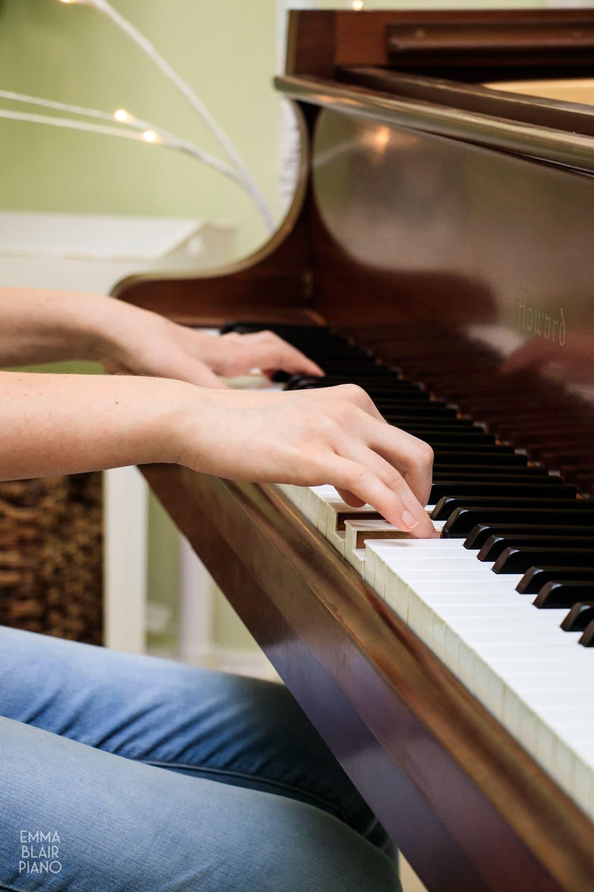 teenage girl playing a brown grand piano