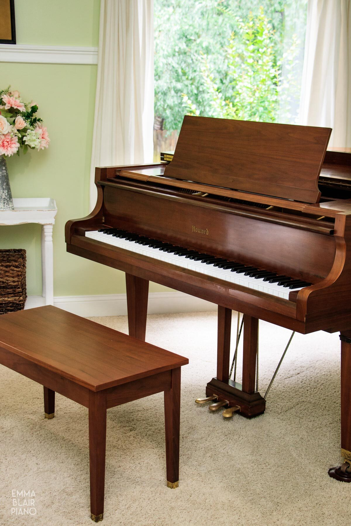 brown grand piano with the piano bench