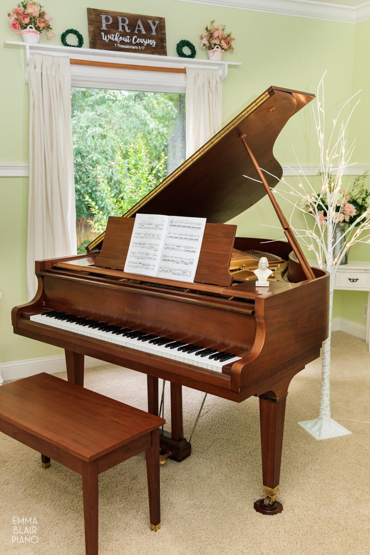 brown grand piano near a window with bouquet of pink flowers and a white tree
