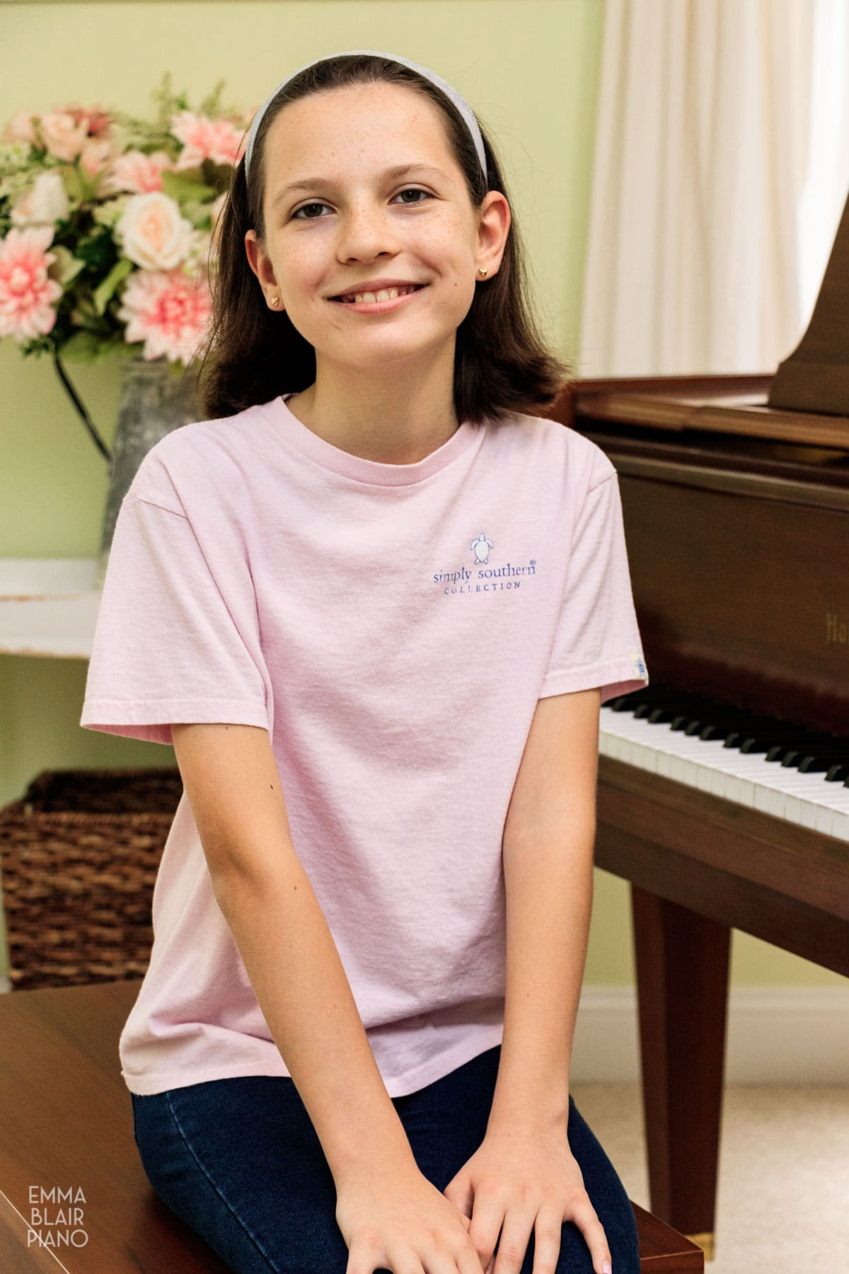 young girl smiling and sitting on the piano bench
