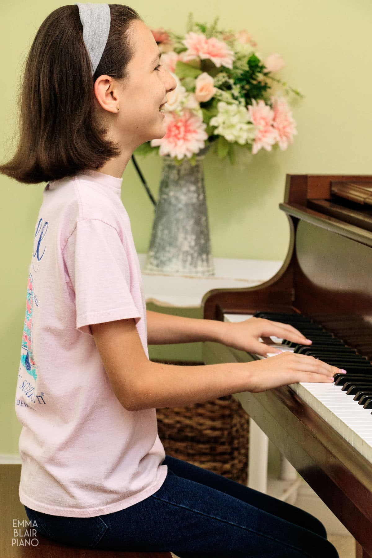 young girl smiling while she plays the piano