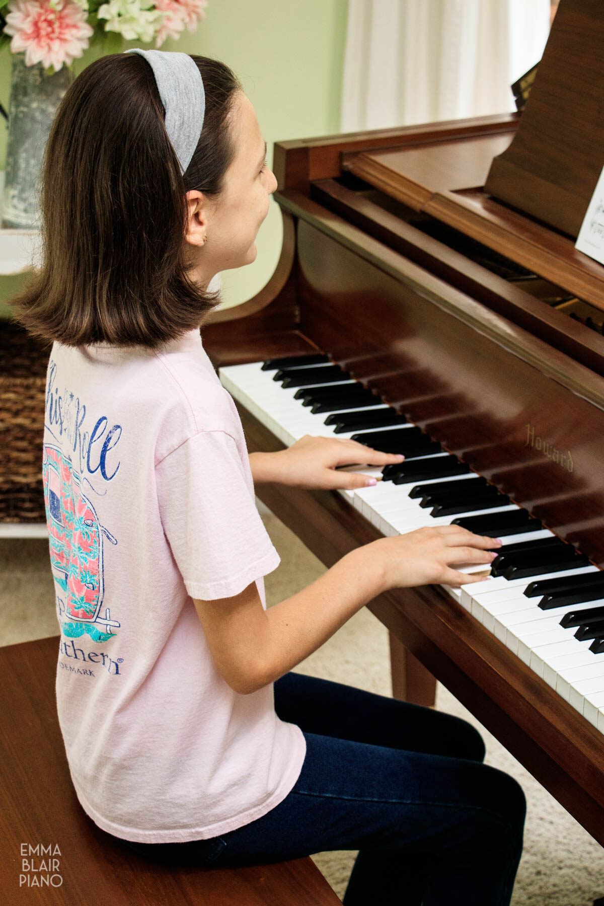 young girl playing a brown baby grand piano